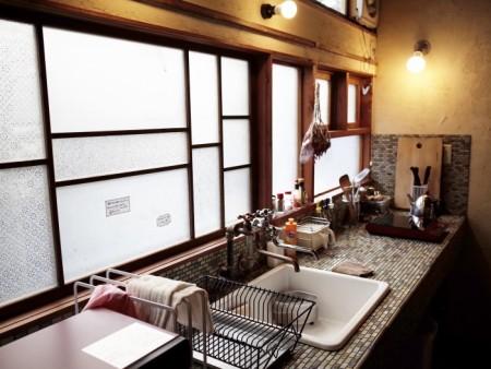 宿泊者が自炊をするための共用キッチン。窓は解体時にあちこちで出たガラスを再利用。